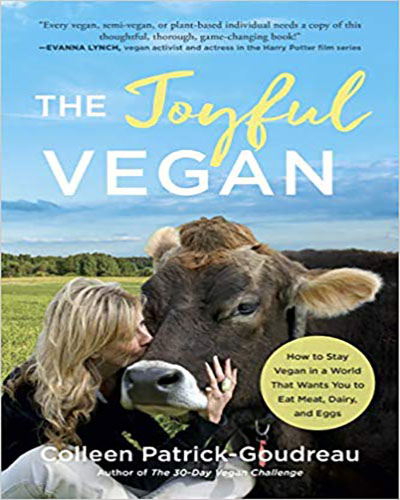 Cover for the book, The Joyful Vegan, featuring the author kissing a cow in a field.