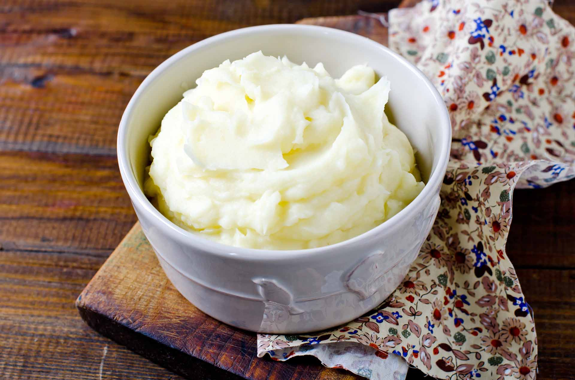 Mashed potatoes in a bowl on a wooden table.