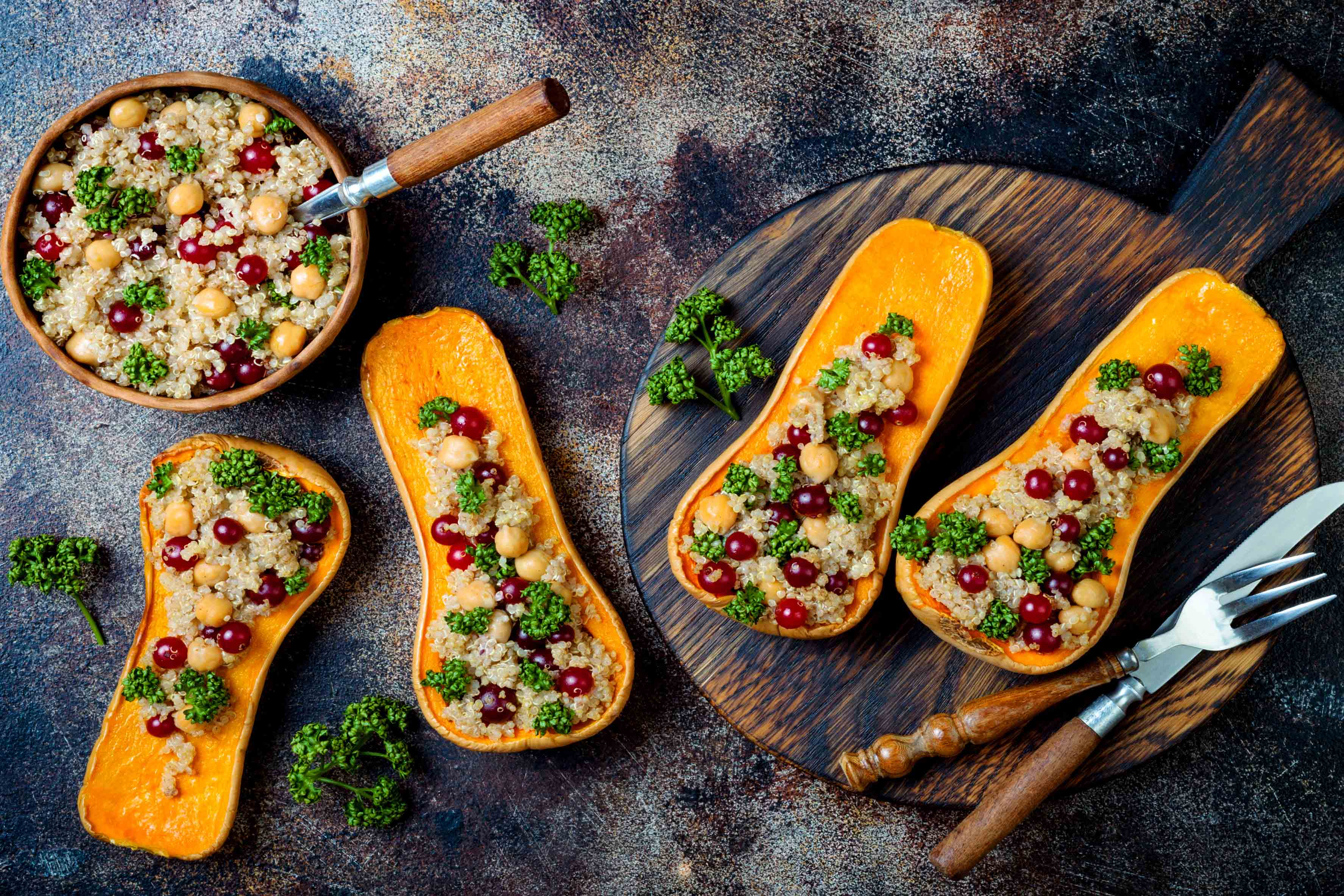 Four butternut squash halves stuffed with quinoa and cranberries sitting on a wooden board on a dark countertop next to a bowl of cranberry quinoa mixture.