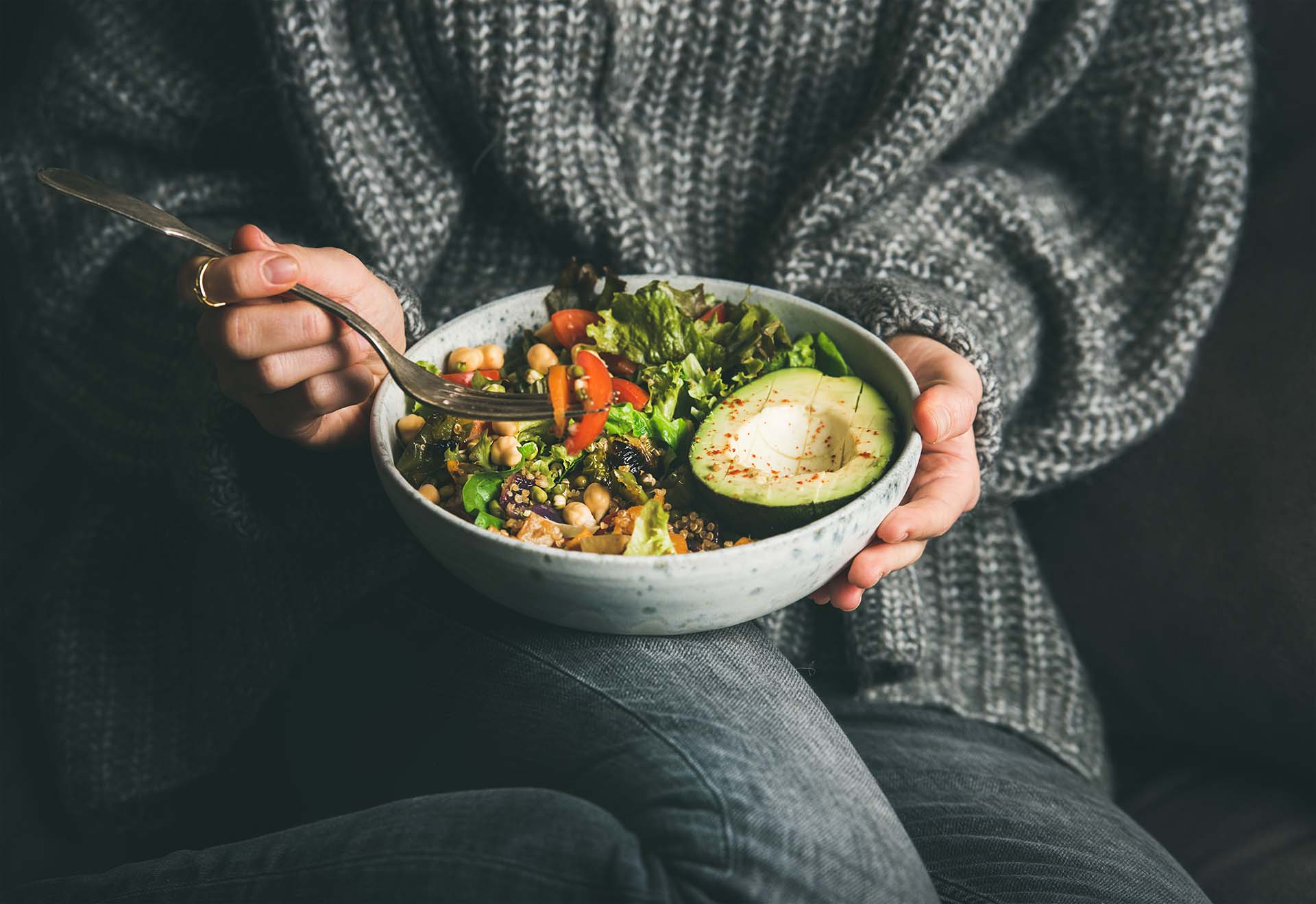 Woman in grey jeans and sweater eating fresh salad, avocado half, grains, beans, roasted vegetables from Buddha bowl.