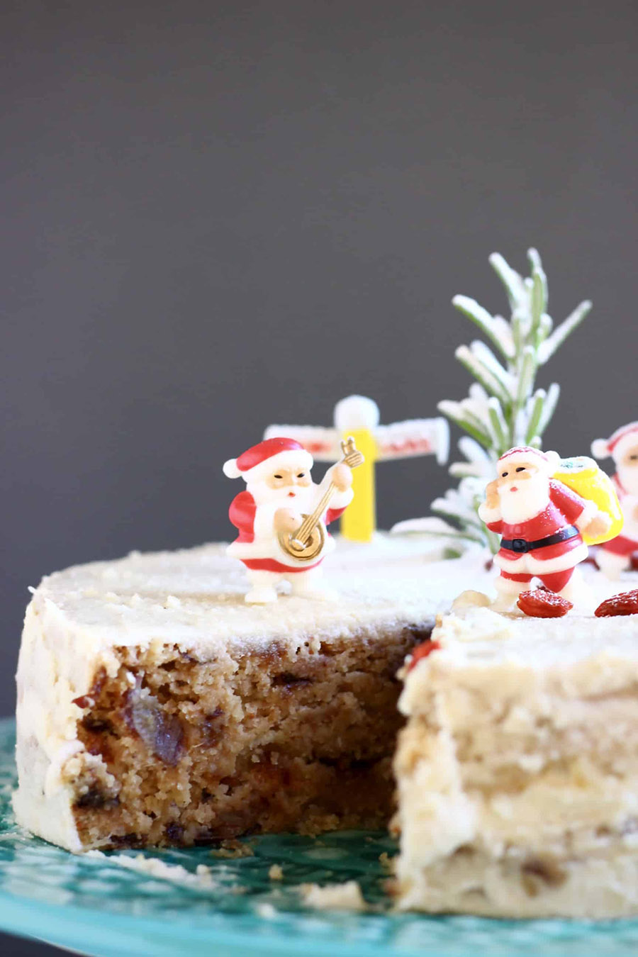 A closeup of an iced fruitcake decorated with miniature santa figurines and dusted with powdered sugar.