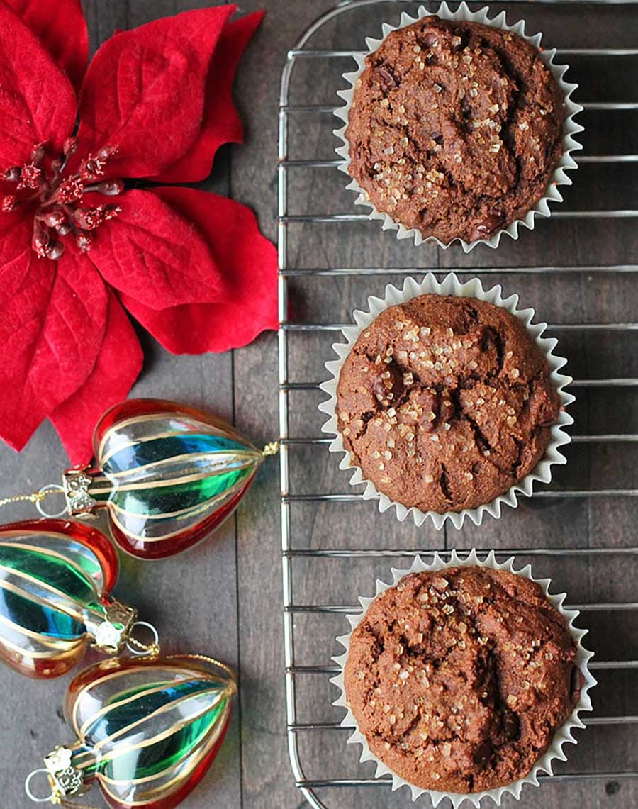 Three muffins on a cooling rack with a flower and holiday ornaments sitting on a wooden table.