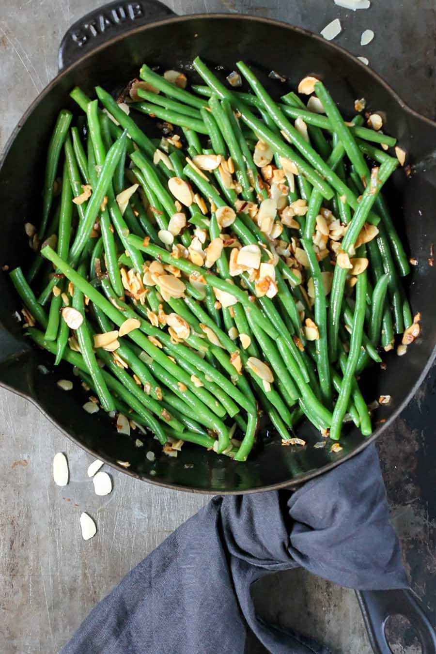 An overhead photo of an iron skillet with green beans sitting on a wooden table.