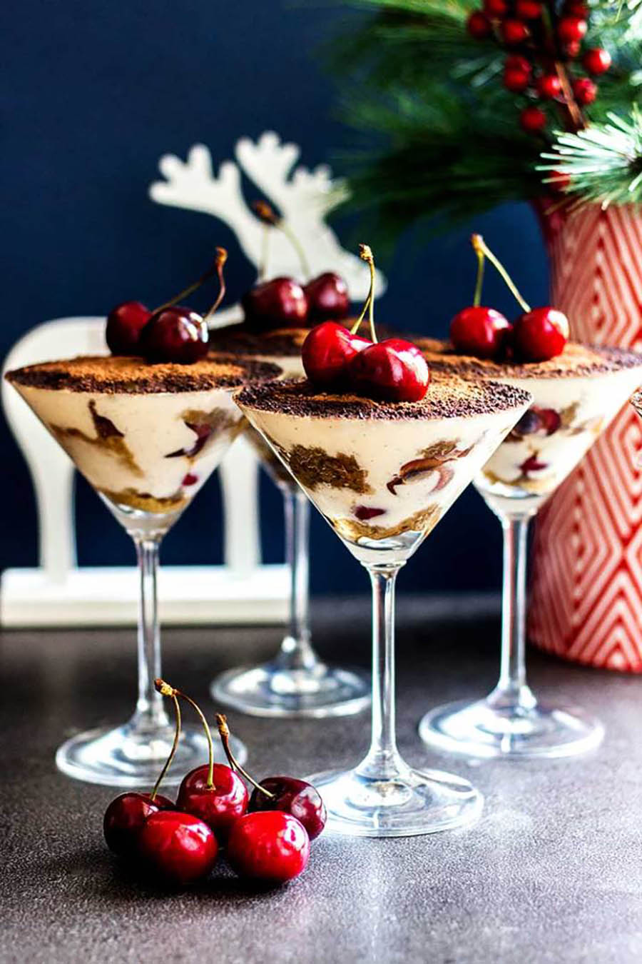 Four servings of tiramisu served in martini glasses with festive red and white decorations in the background.