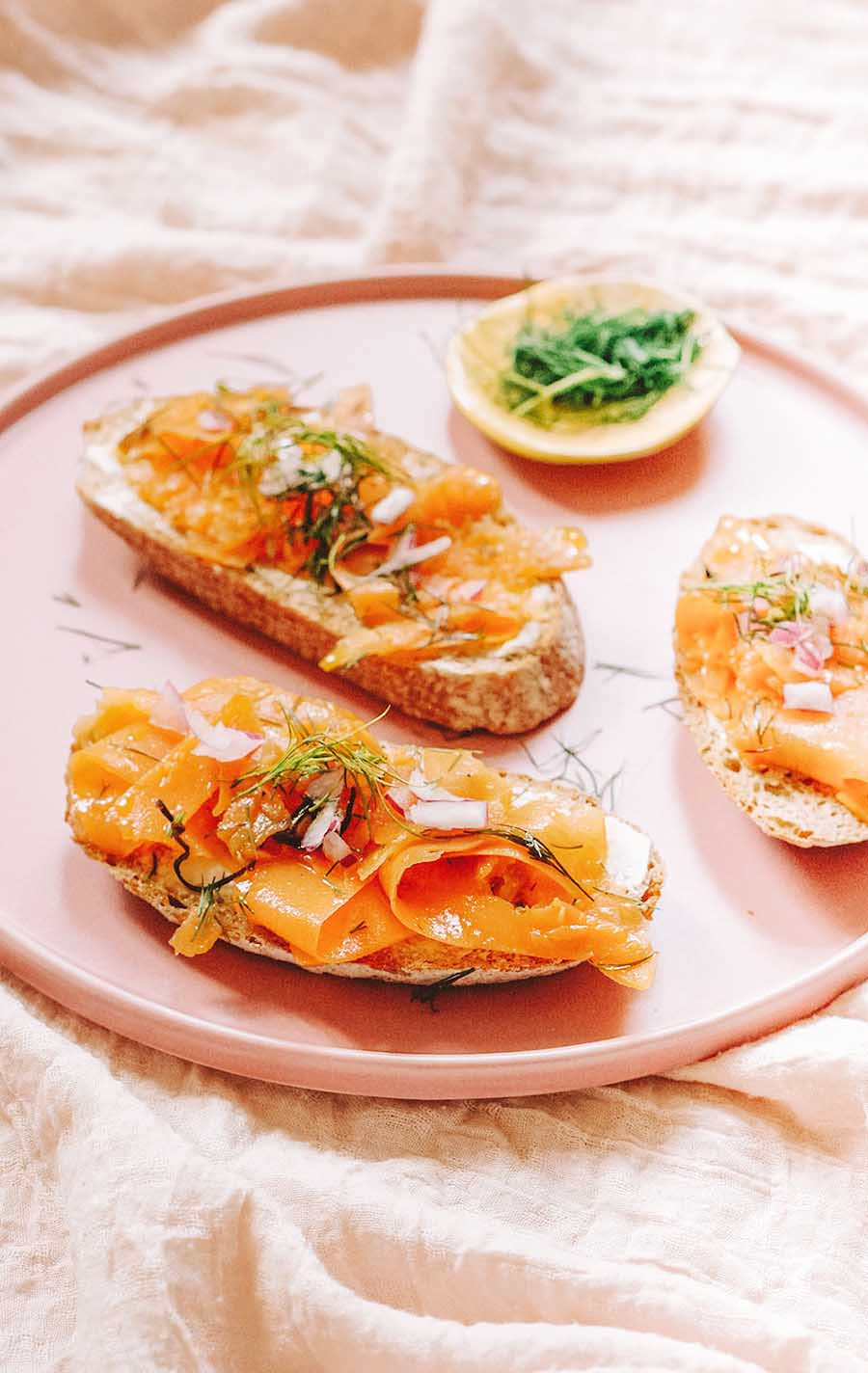 A pink plate with three pieces of toast topped with vegan smoked salmon.