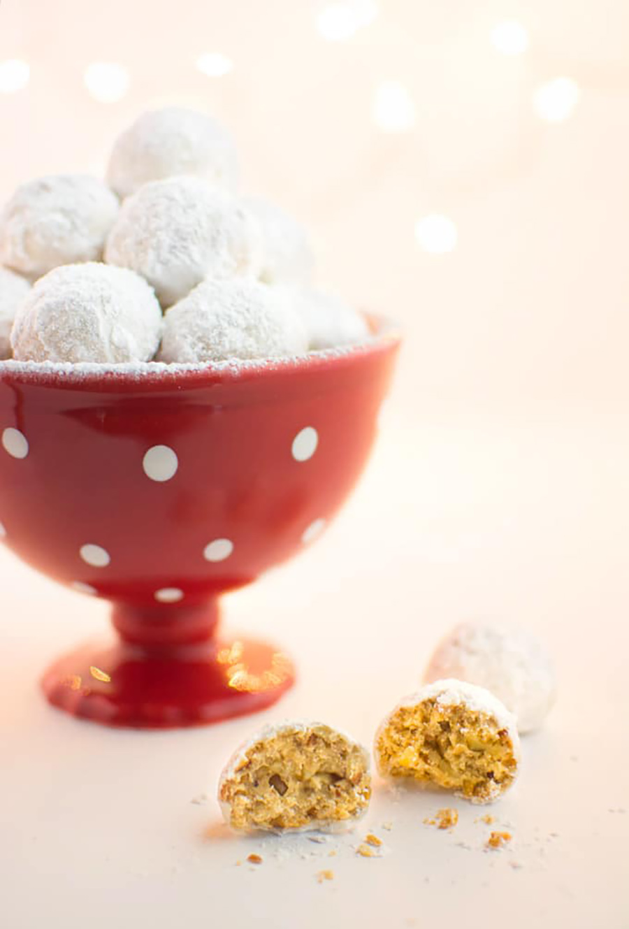 A red cup with white polka dots filled with snowball cookies sitting on a counter with one cookie broken open sitting in front.