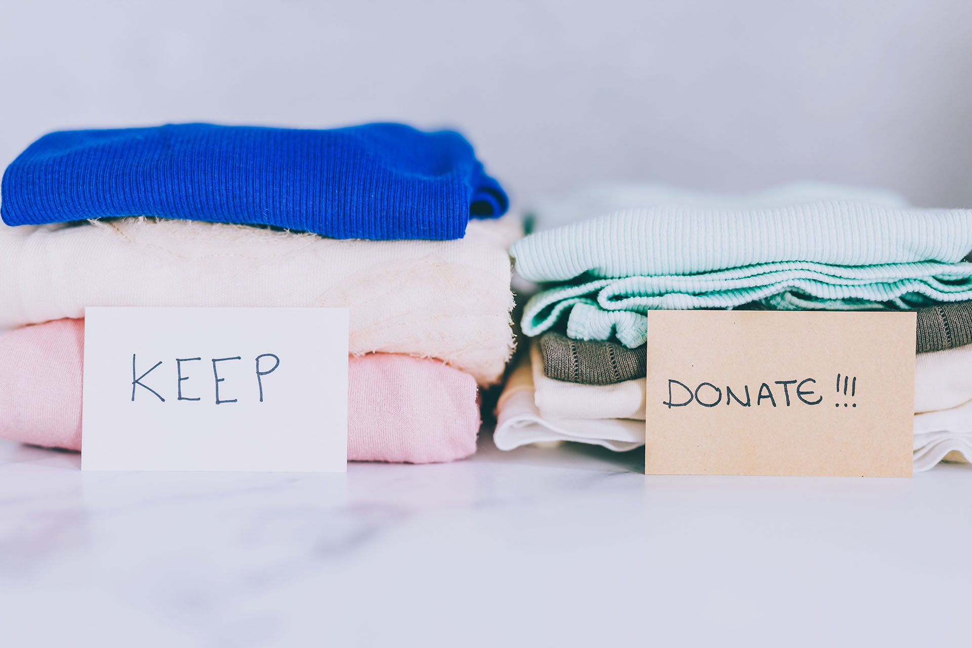 Piles of t-shirts and clothes being sorted into Keep Discard and Donate categories
