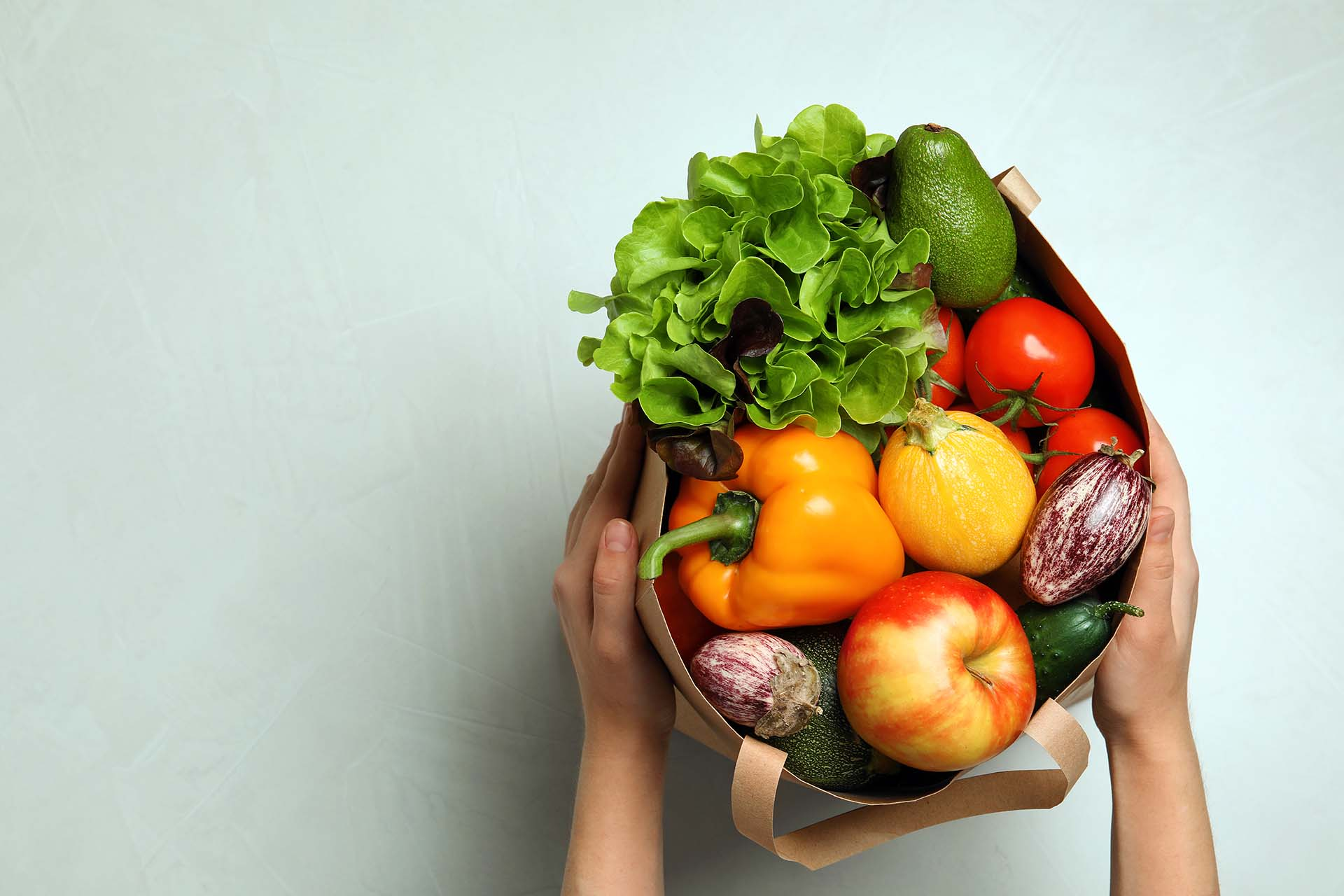 Woman holding paper bag with fresh vegetables and fruits.