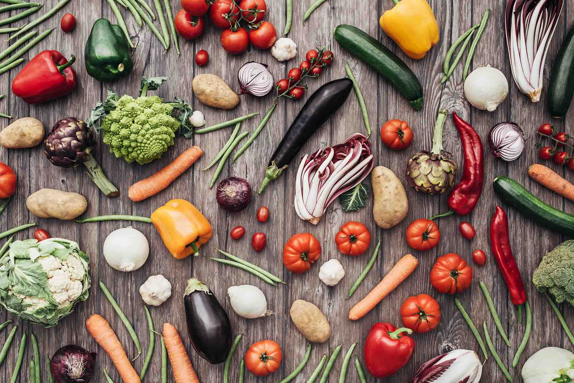 Fresh colorful organic vegetables on a rustic wooden table background.