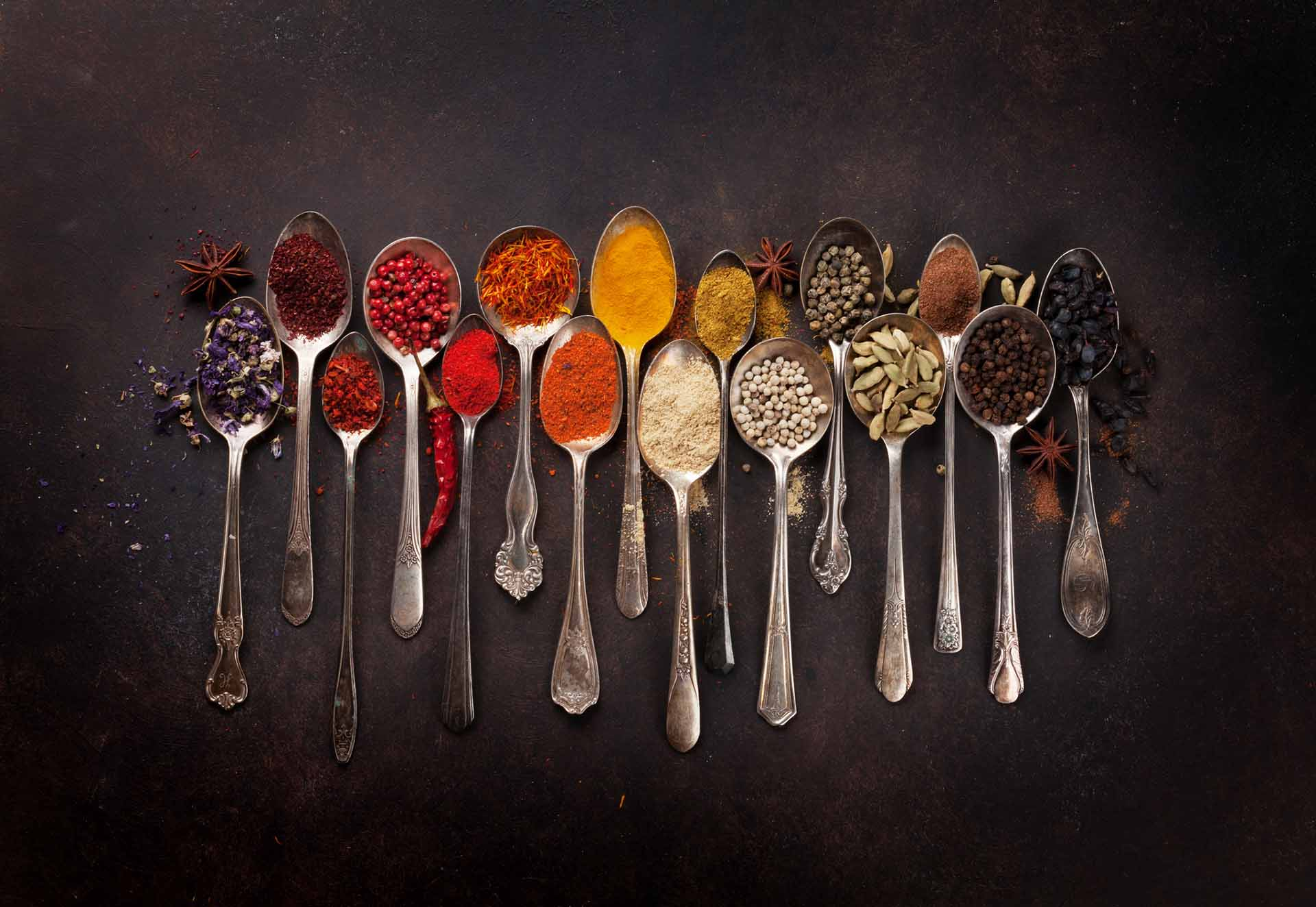 Various spices spoons on stone table.