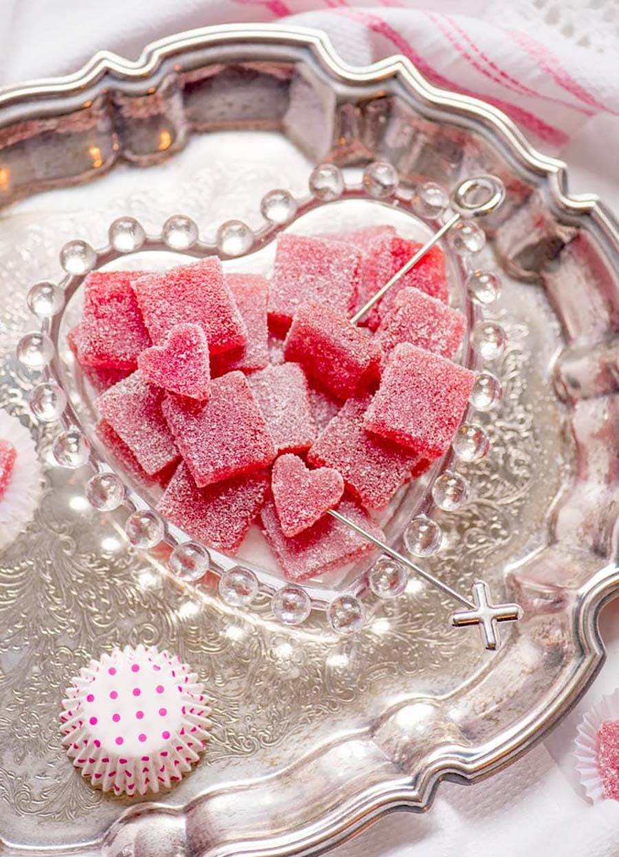 A glass heart-shaped dish holding red Strawberry Pate de Fruit candies sitting on a silver tray.