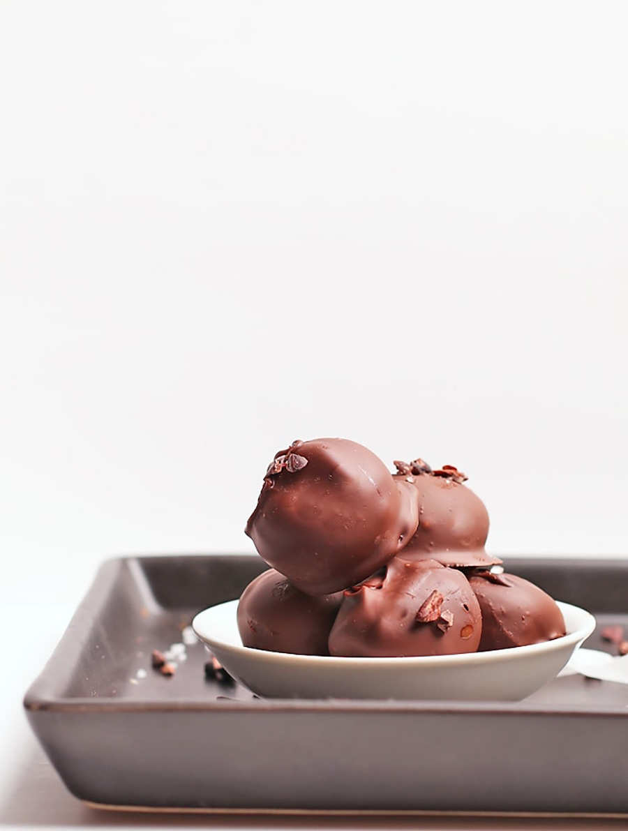 A white bowl of chocolate truffles sitting on a baking tray with a white background.