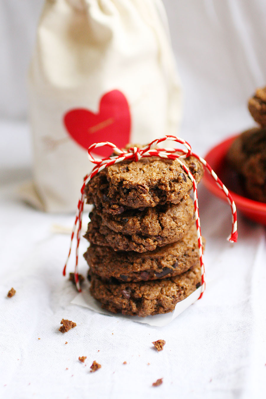 A stack of cookies tied with red and white bakers string sitting on a white table with a red bowl of cookies and a cream bag with a red heart in the background
