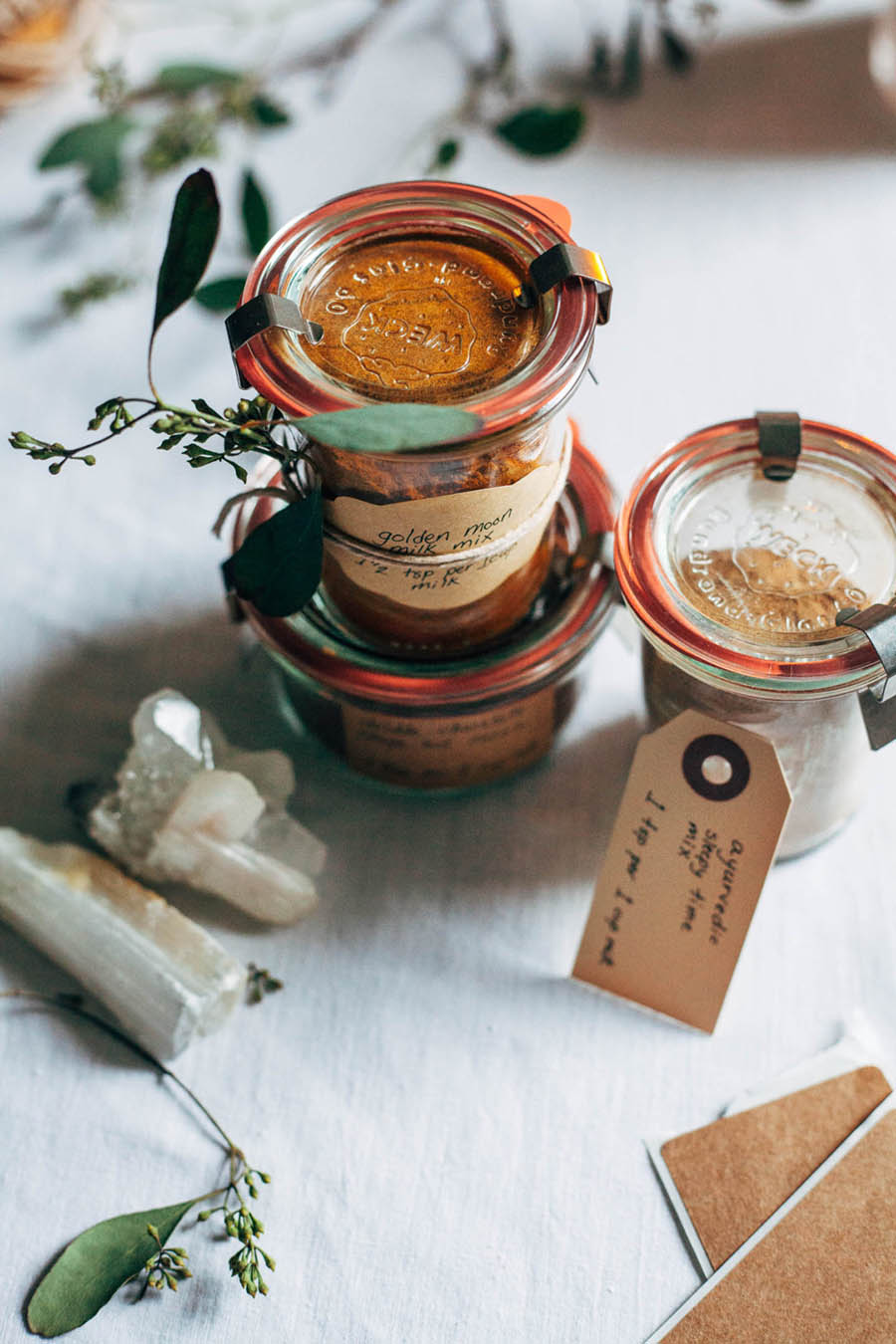 Three jars of homemade tea spices sitting on a table with rustic garnishes.