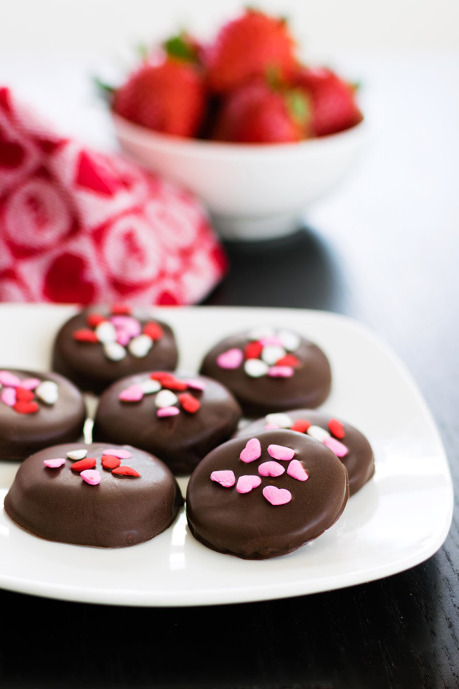 A white plate full of chocolate covered treats sitting on a wooden table with a pink and red napkin and a bowl of strawberries in the background.