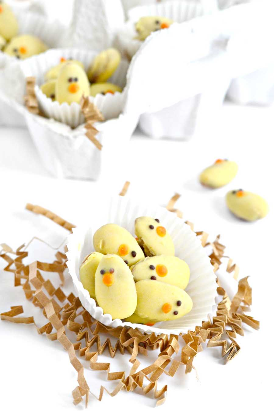 """Cute decorated almond """"chicks"""" sitting in a white cupcake liner with crinkled decoration laying around."""