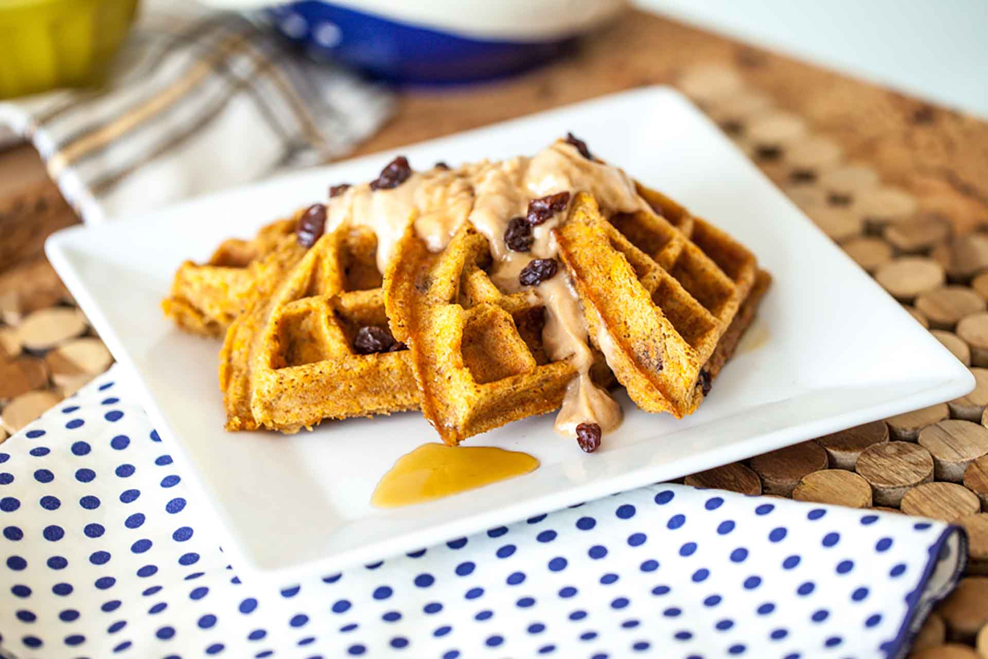 A plate of waffles sitting on a wooden table.