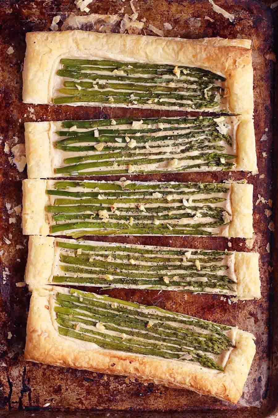 A large tart topped with asparagus and cut into long slices sitting on top of a well-seasoned cooking tray.