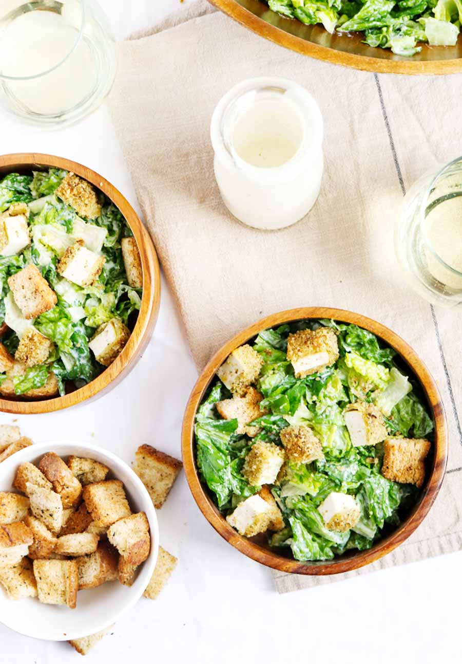Two bowls of salad sitting on a table with a jar of dressing and a dish of croutons sitting nearby.
