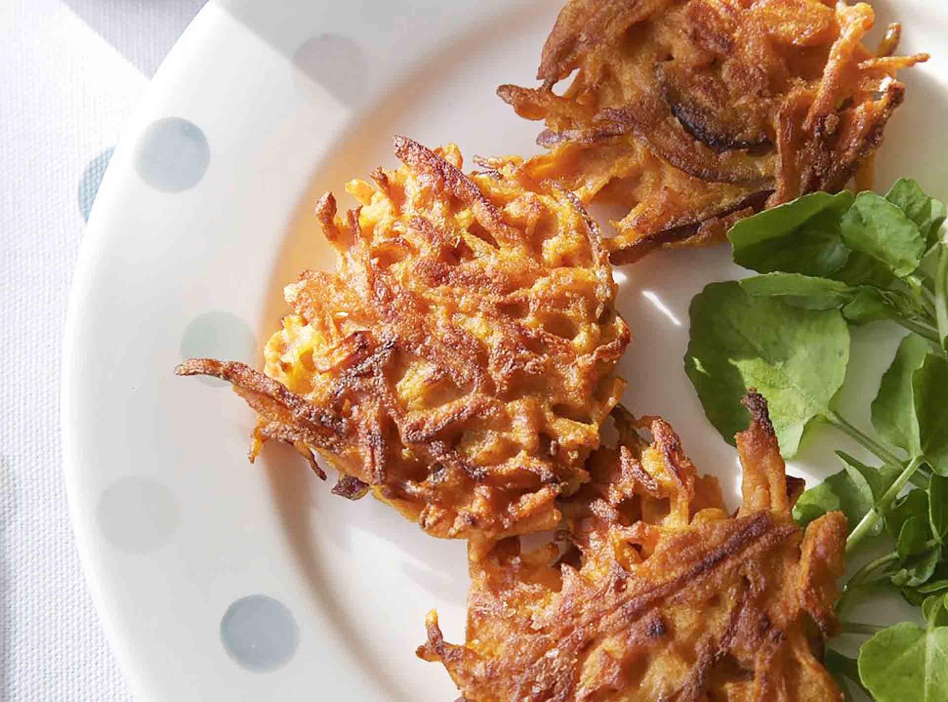Three carrot fritters sitting on a white plate with a few decorative greens.