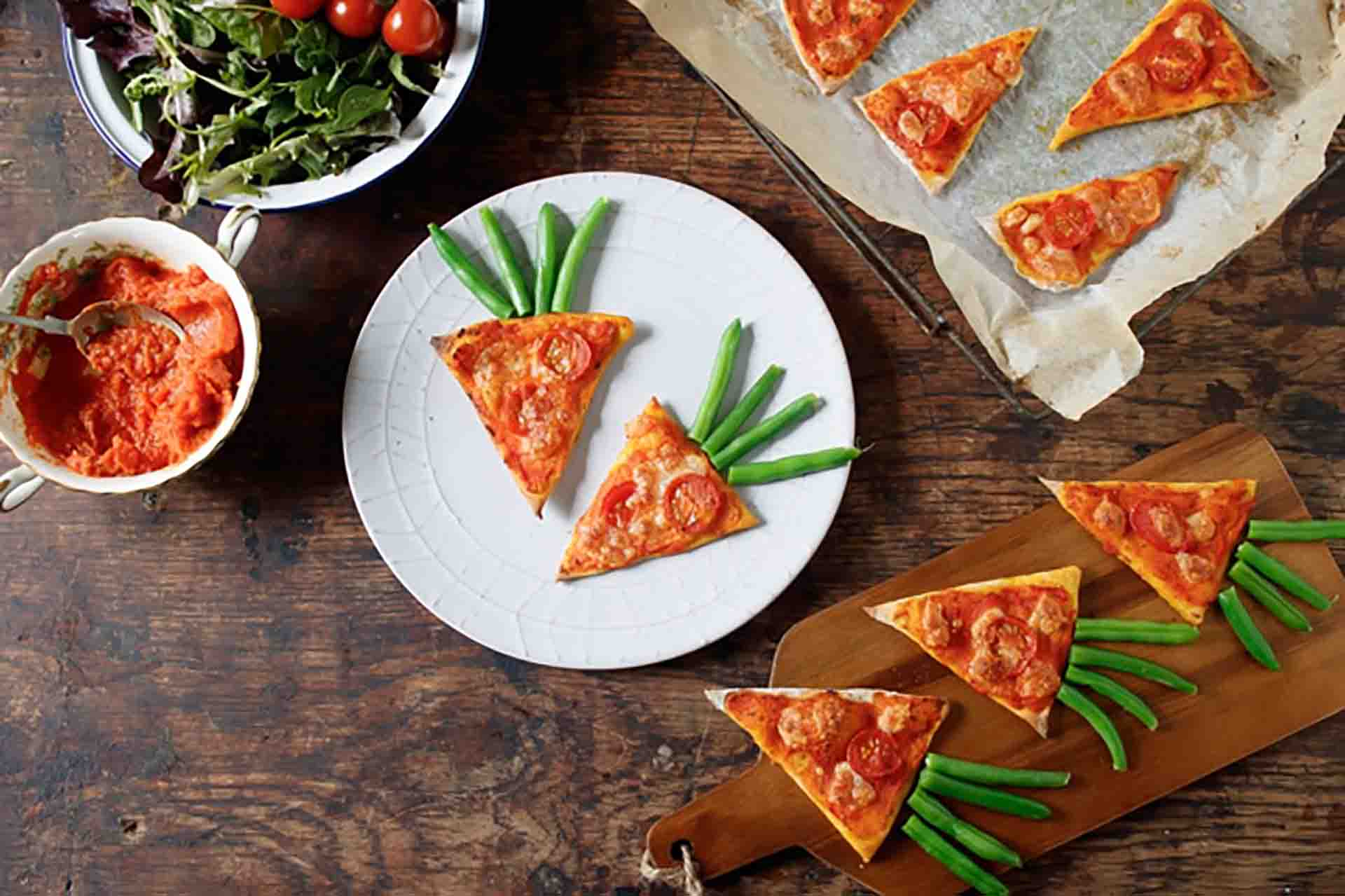 Two slices of carrot pizza on a plate sitting on a wooden table with more pizza on wooden boards.