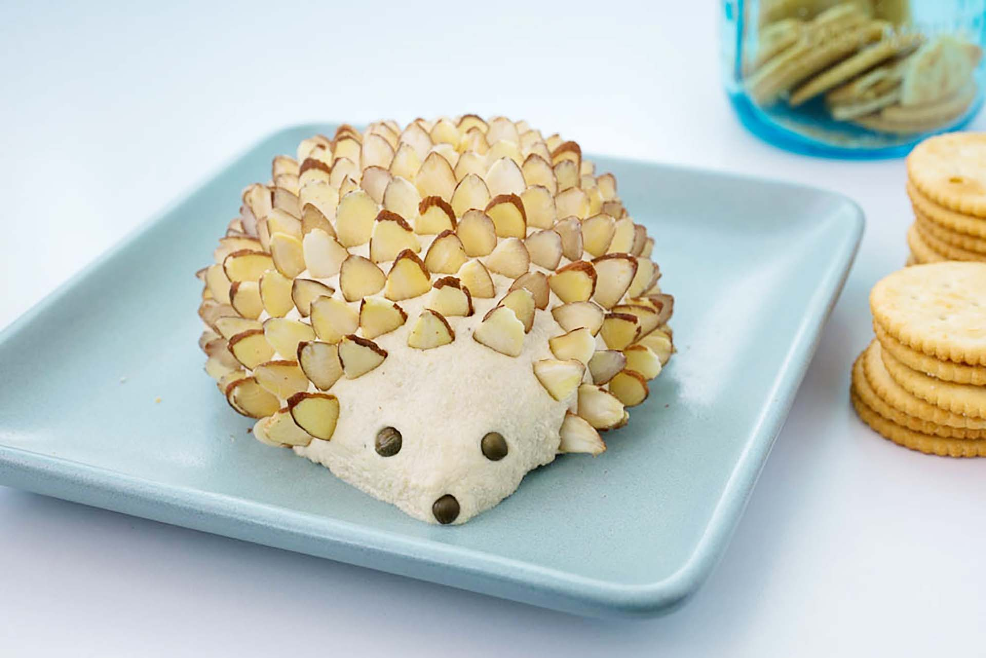 A cheeseball decorated to look like a hedgehog sitting on a blue plate with a couple of stacks of crackers nearby.