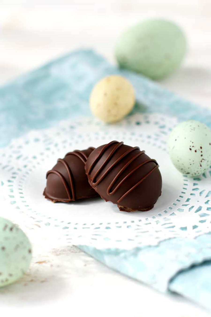 Two chocolate easter eggs sitting on a white doily which is placed on top of a light blue cloth napkin with a few pastel-colored eggs laying around.