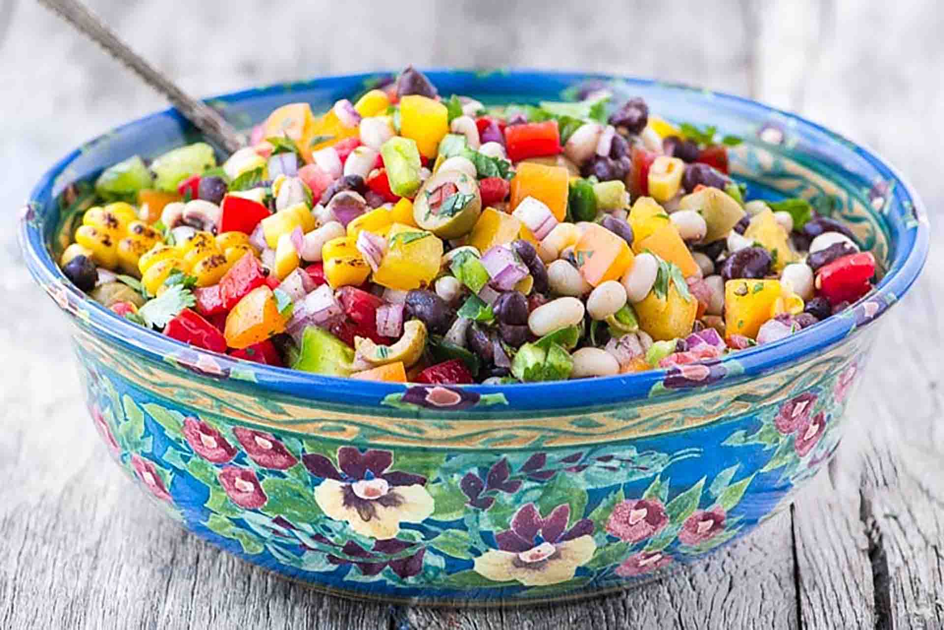 Corn and bean salad in a colorful bowl sitting on a wooden table.
