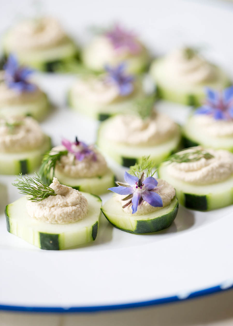 A white plate full of cucumber canapes.