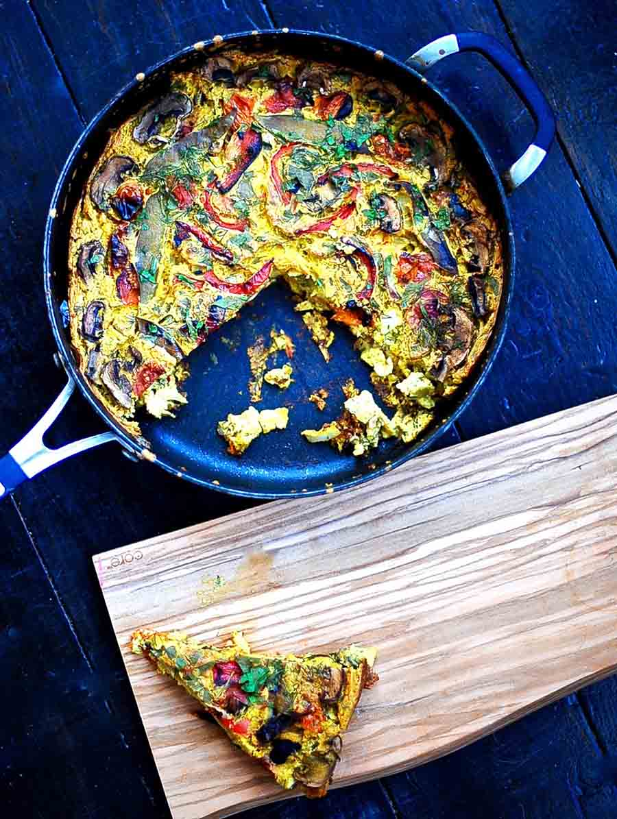 An overhead view of a vegetable frittata in a pan with a slice taken out and sitting next to it on a wooden board.