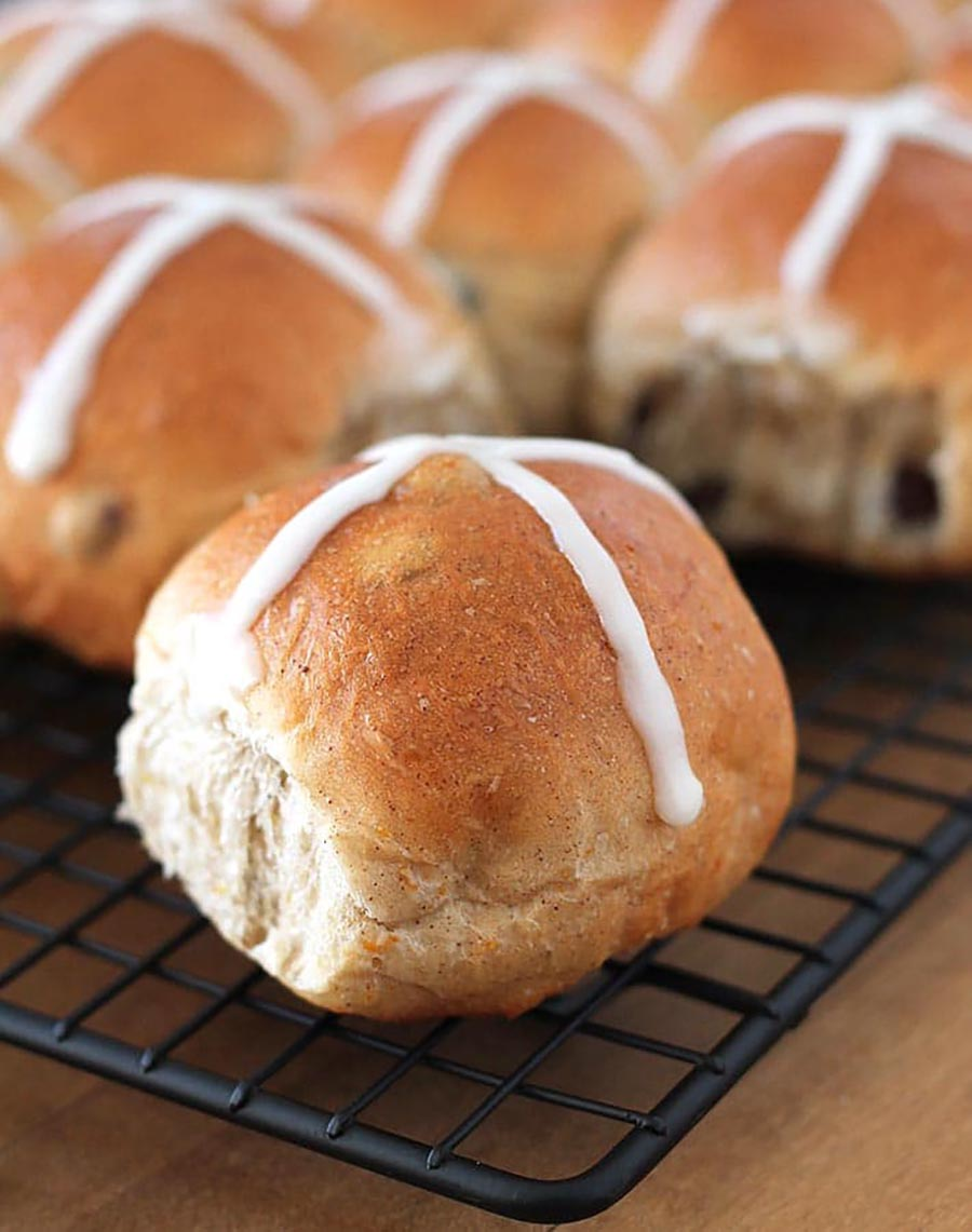 Closeup of a group of hot cross buns sitting on a cooling rack.