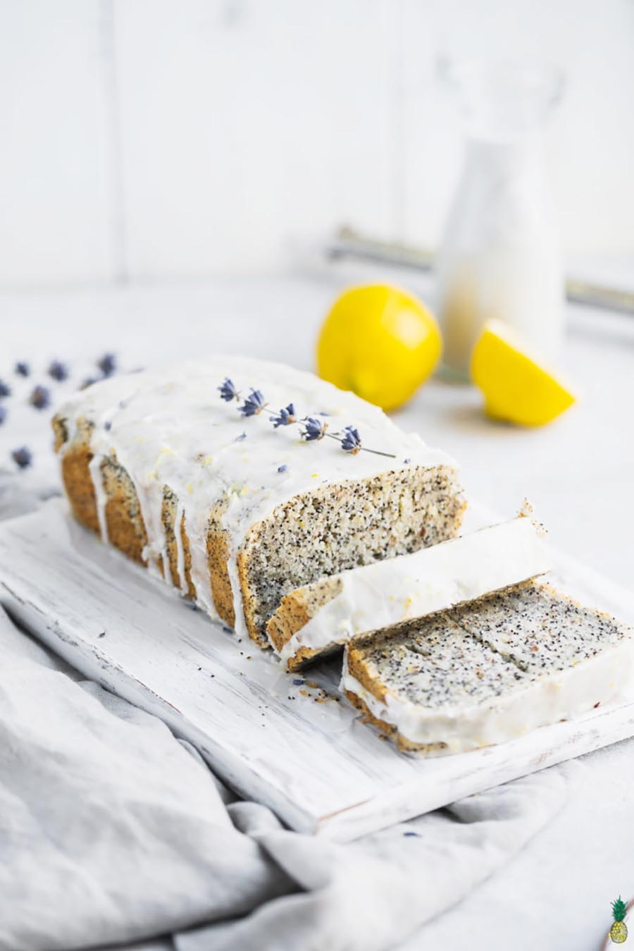 A loaf of poppyseed bread with icing sitting on a white plate with a lemon and vegan milk in the background.