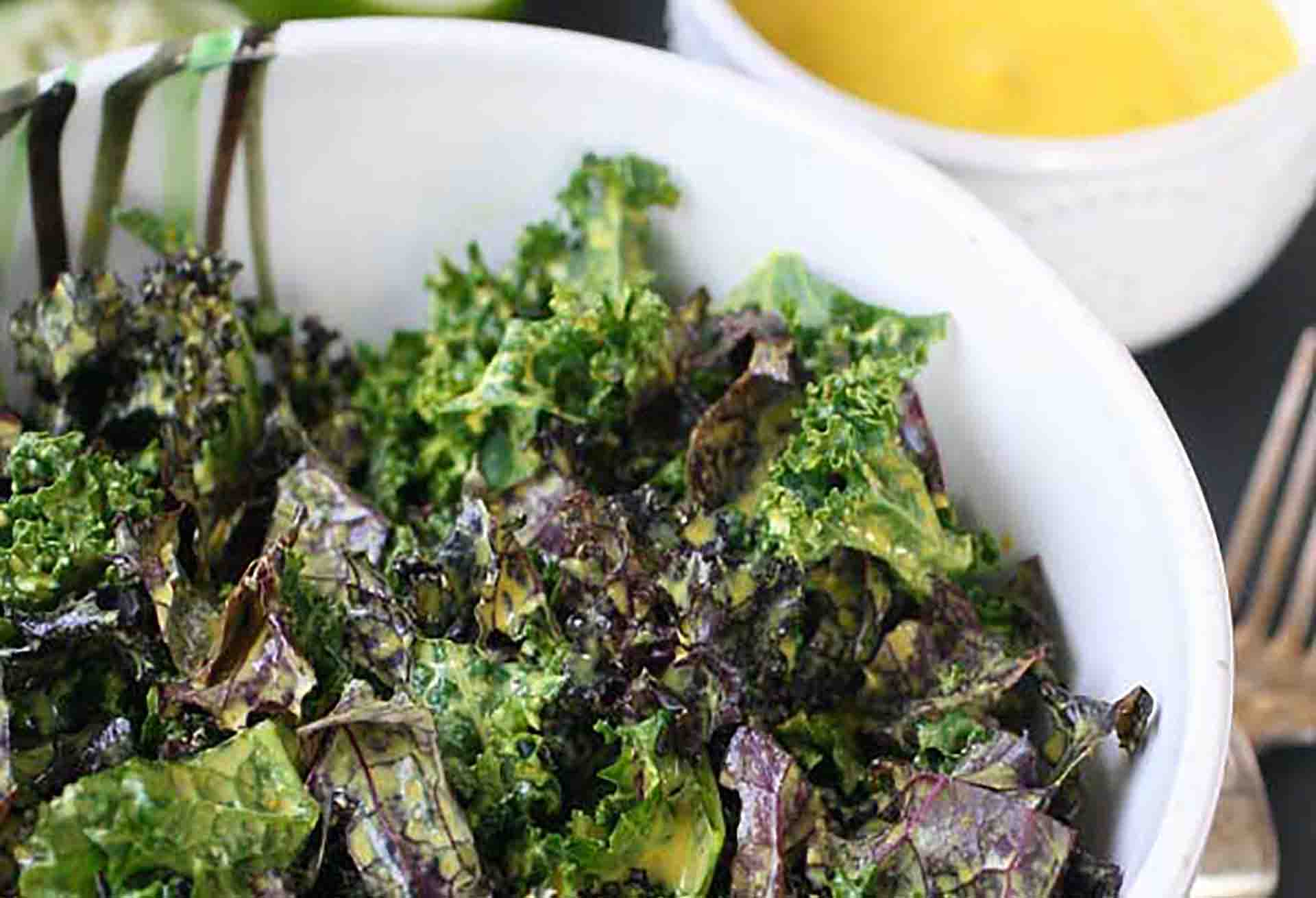 Closeup of a bowl of kale salad with a bowl of dressing in the background.