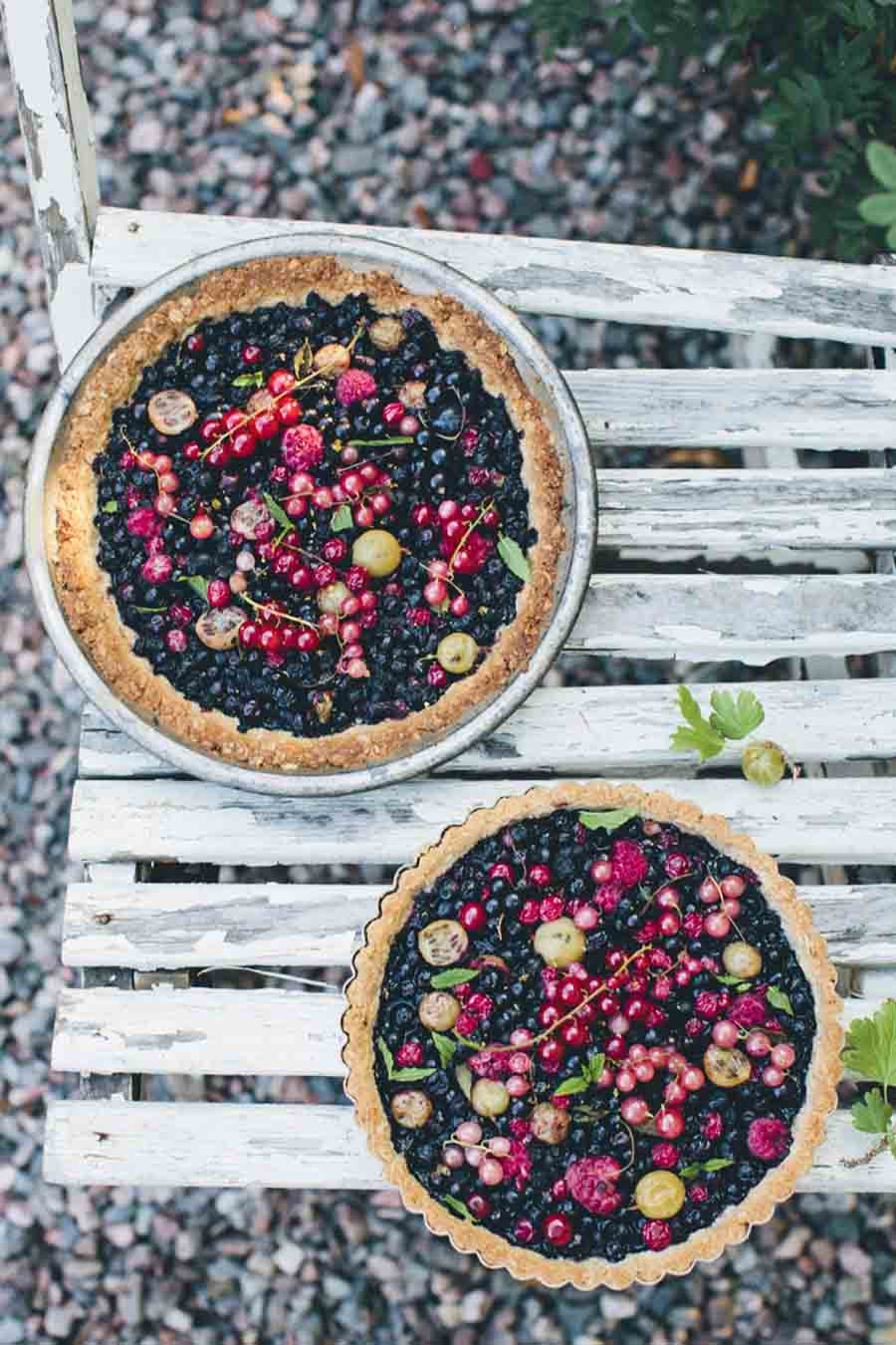 Overhead view of two mixed berry tarts sitting on a rustic wooden chair in a gravel walkway.