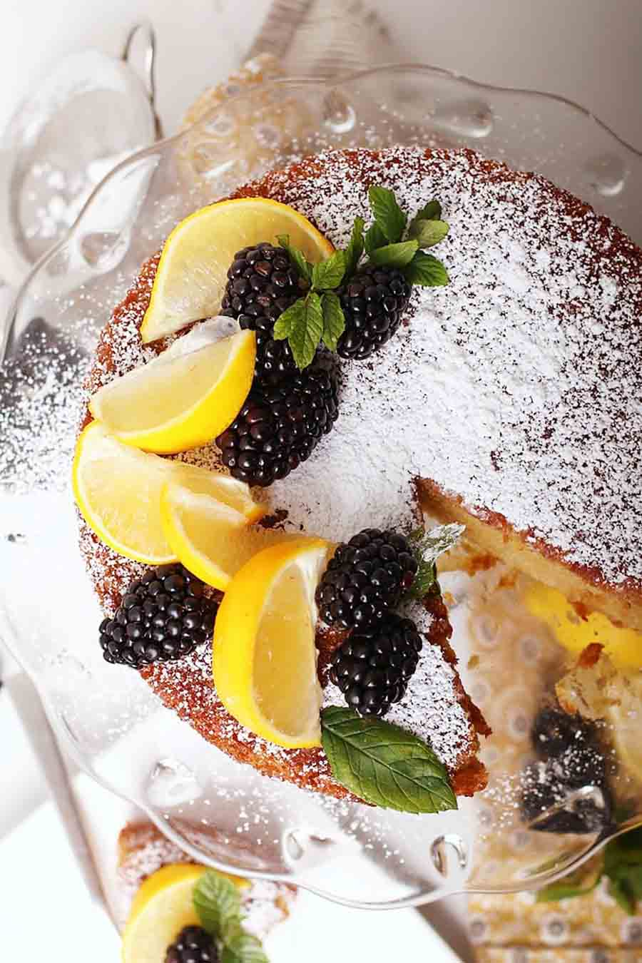 Overhead view of an olive oil cake with a slice missing that is decorated with fresh lemon wedges and blackberries with powdered sugar dusted on top.