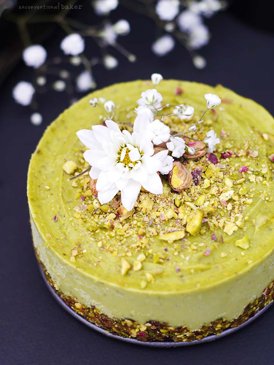 A pistachio green cake with a white flower decoration sitting on a dark countertop.