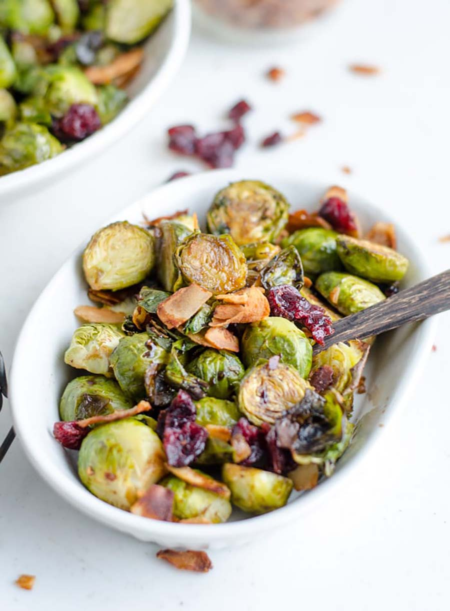 A white dish full of roasted brussel sprouts with a serving spoon sitting in the bowl. Another bowl is in the background.