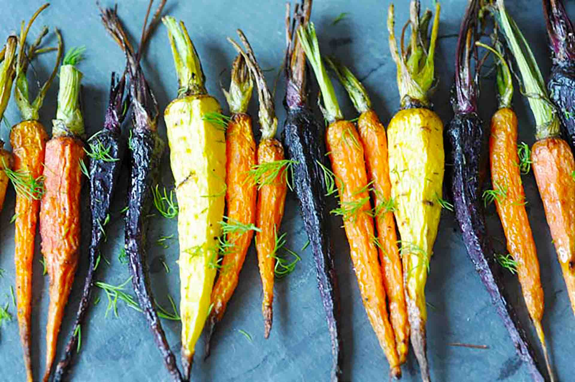 A tray of whole roasted colorful carrots.