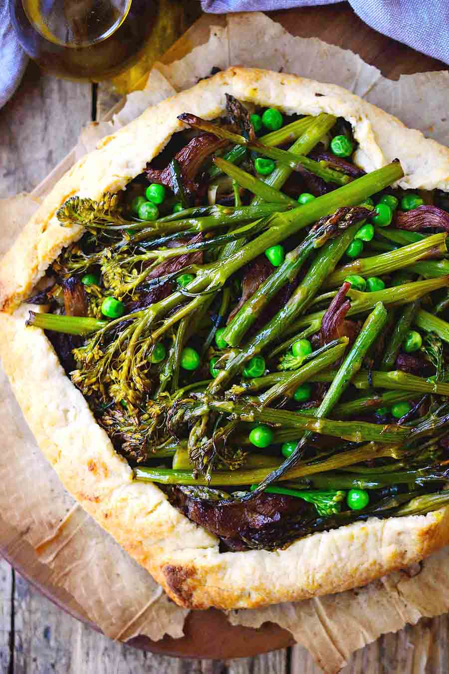 Closeup view of a cooked galette with peas and brocollini on top.