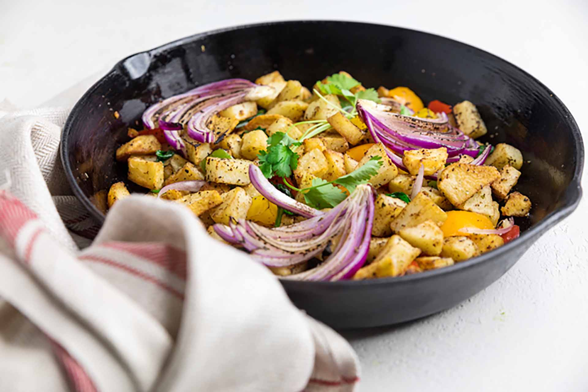 An iron skillet filled with roasted potatoes and vegetables sitting on a white countertop.