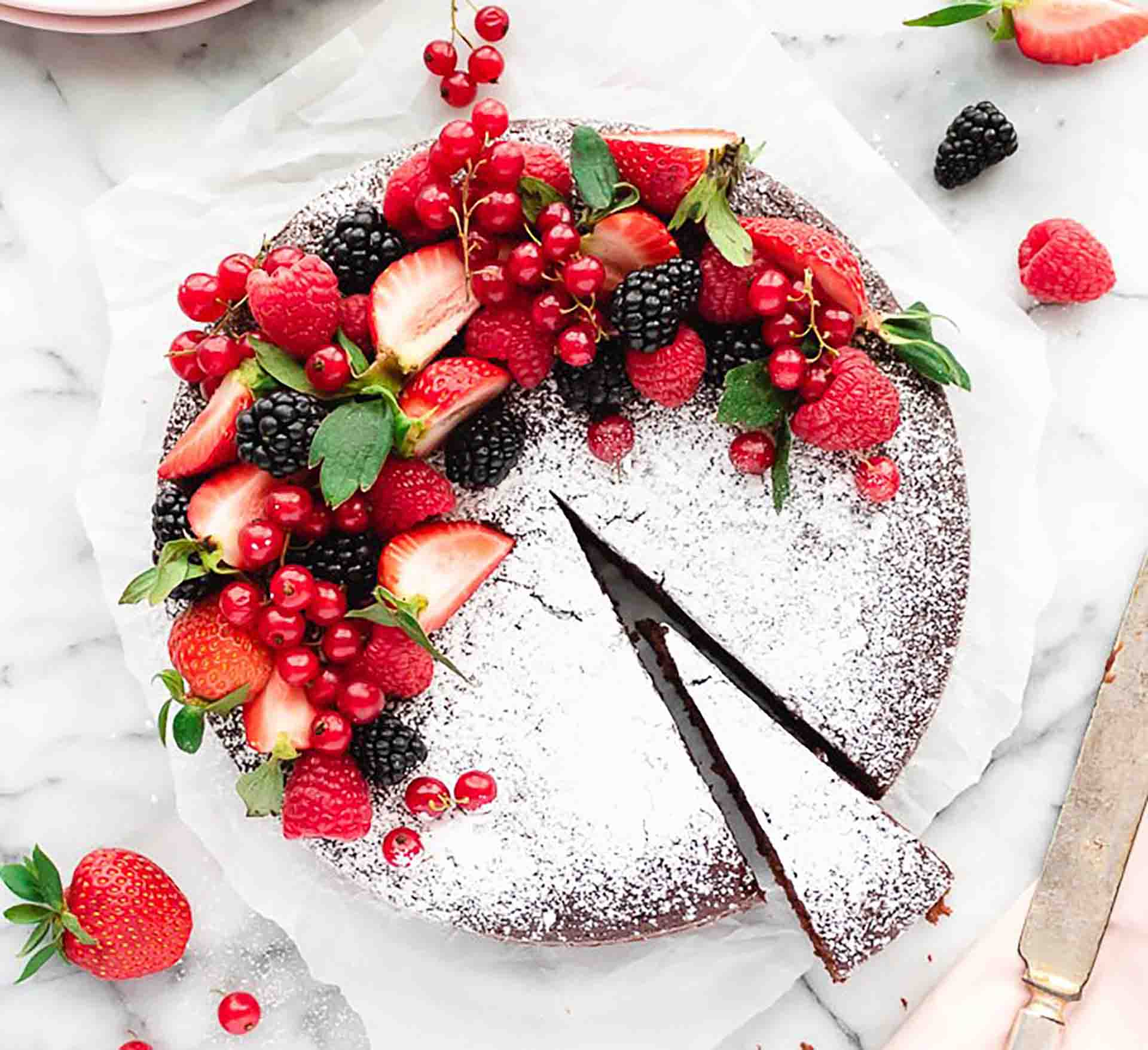 A chocolate cake decorated with various fresh fruits and dusted with powdered sugar.