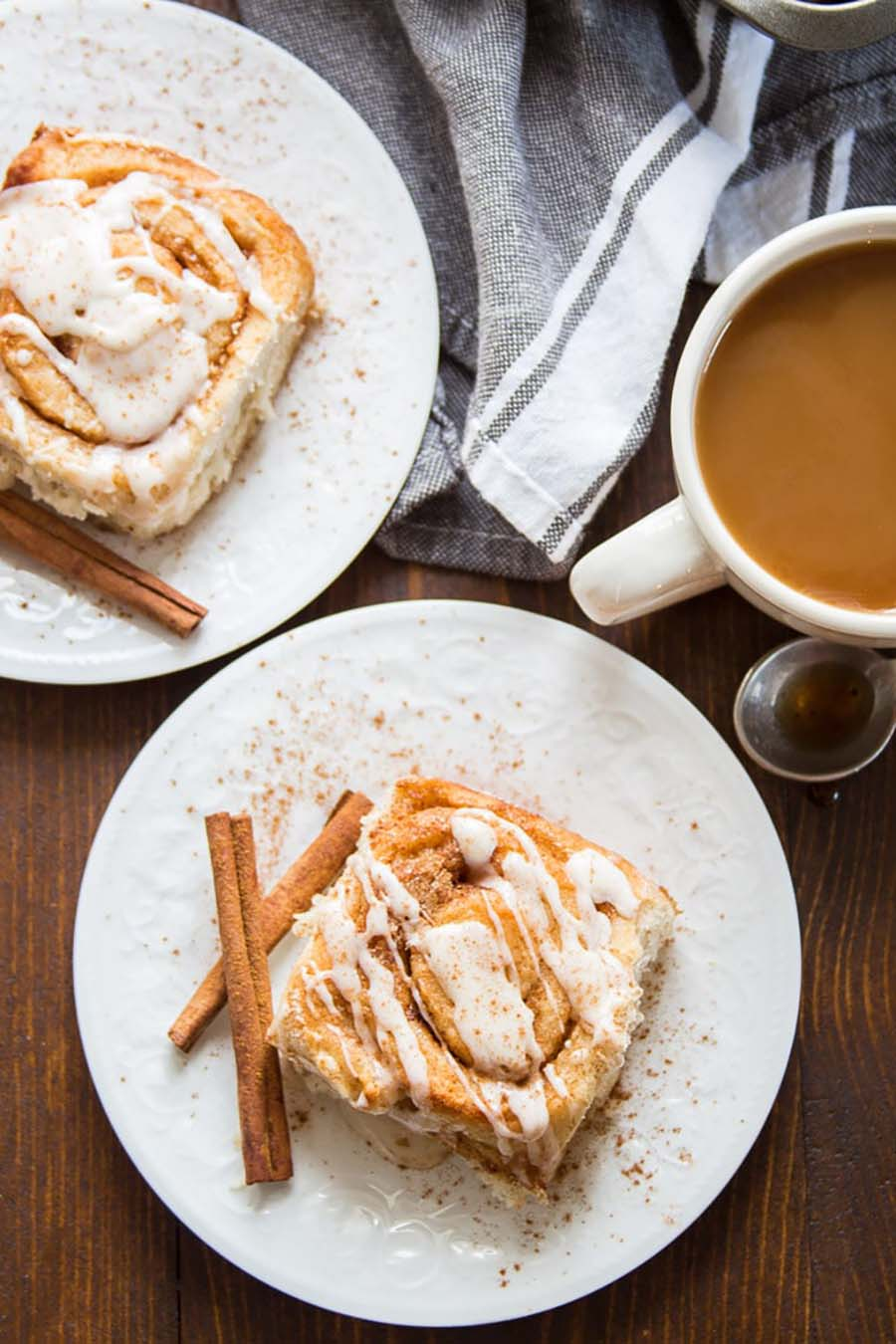 An overhead view of two plates with large cinnamon rolls on them with a cup of coffee sitting nearby.