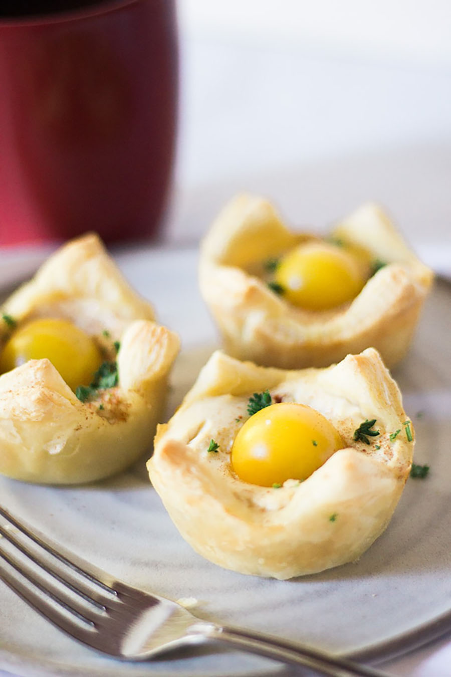 A plate of three vegan egg cups sitting on a table with a fork leaned upon the plate.