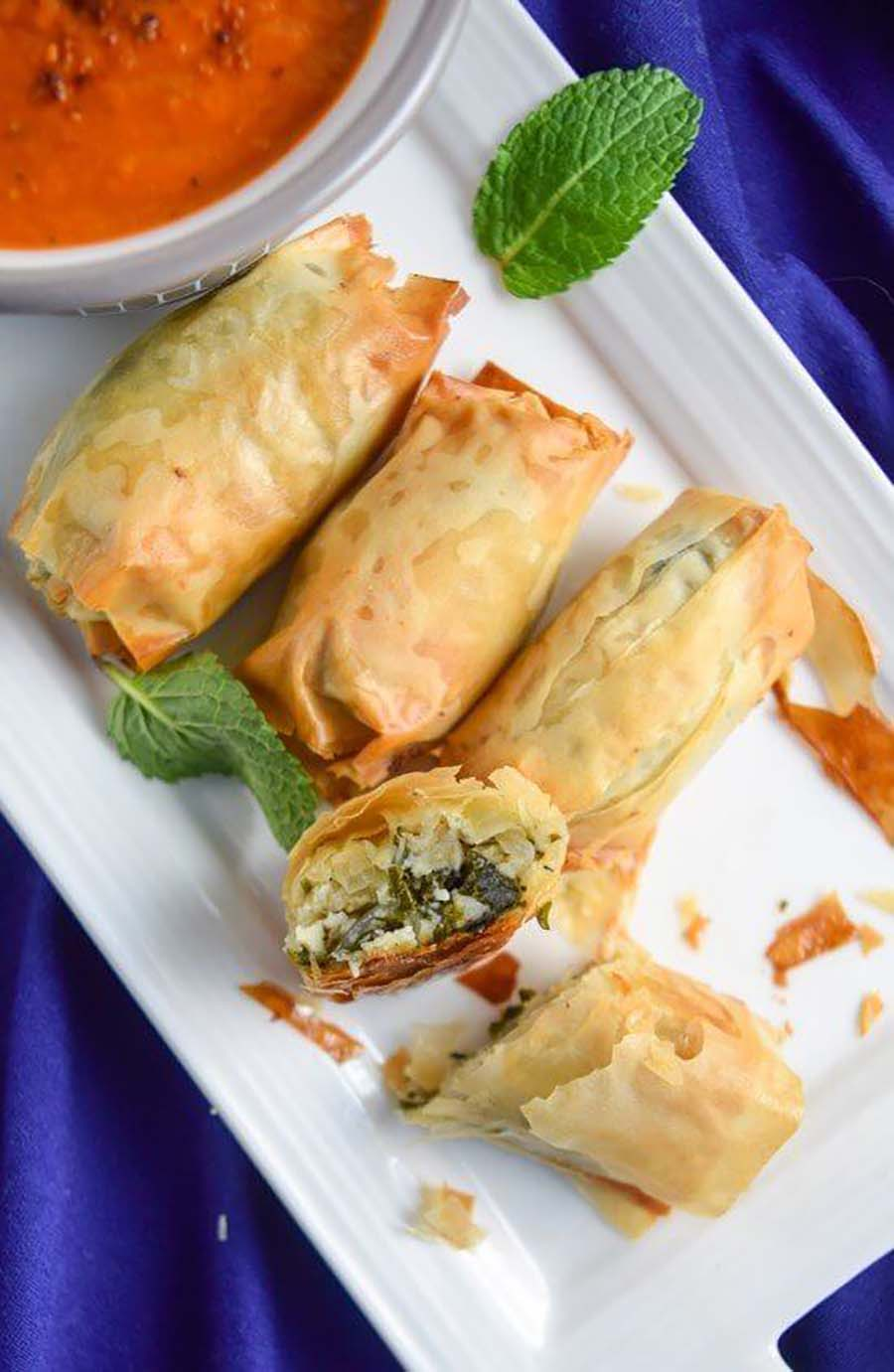Overview of four spanakopita sitting on a white plate with a blue background.
