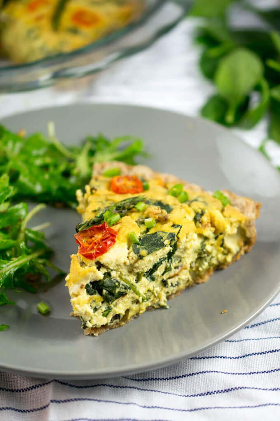 A slice of tofu chickpea quiche sitting on a plate next to a serving of greens.