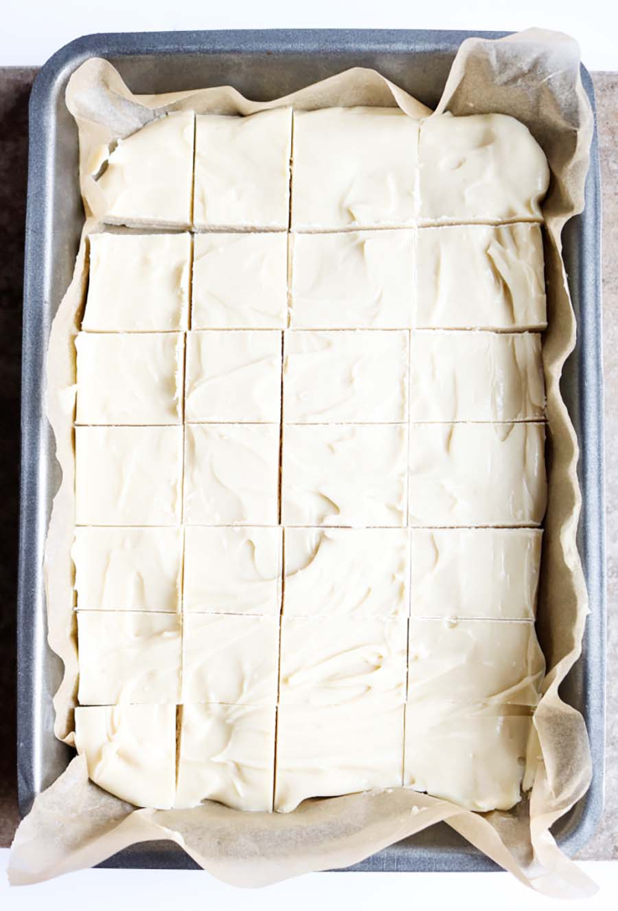 Overhead view of a pan of white chocolate fudge cut into squares.