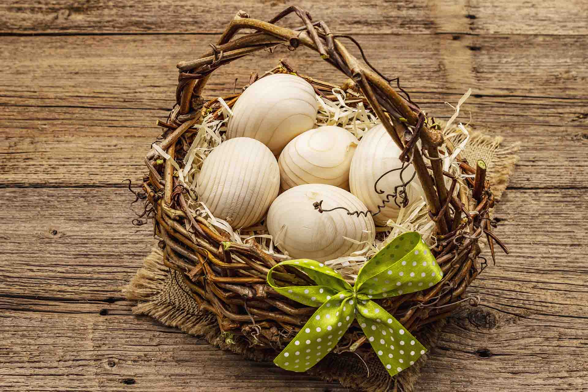 A wooden basket with a green bow filled with wooden eggs sitting on a wooden table.