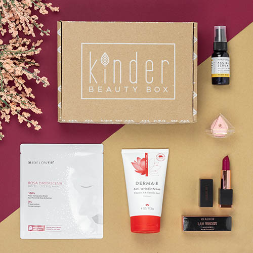 A Kinder Beauty Box with various products displayed around it sitting on a red and gold background.