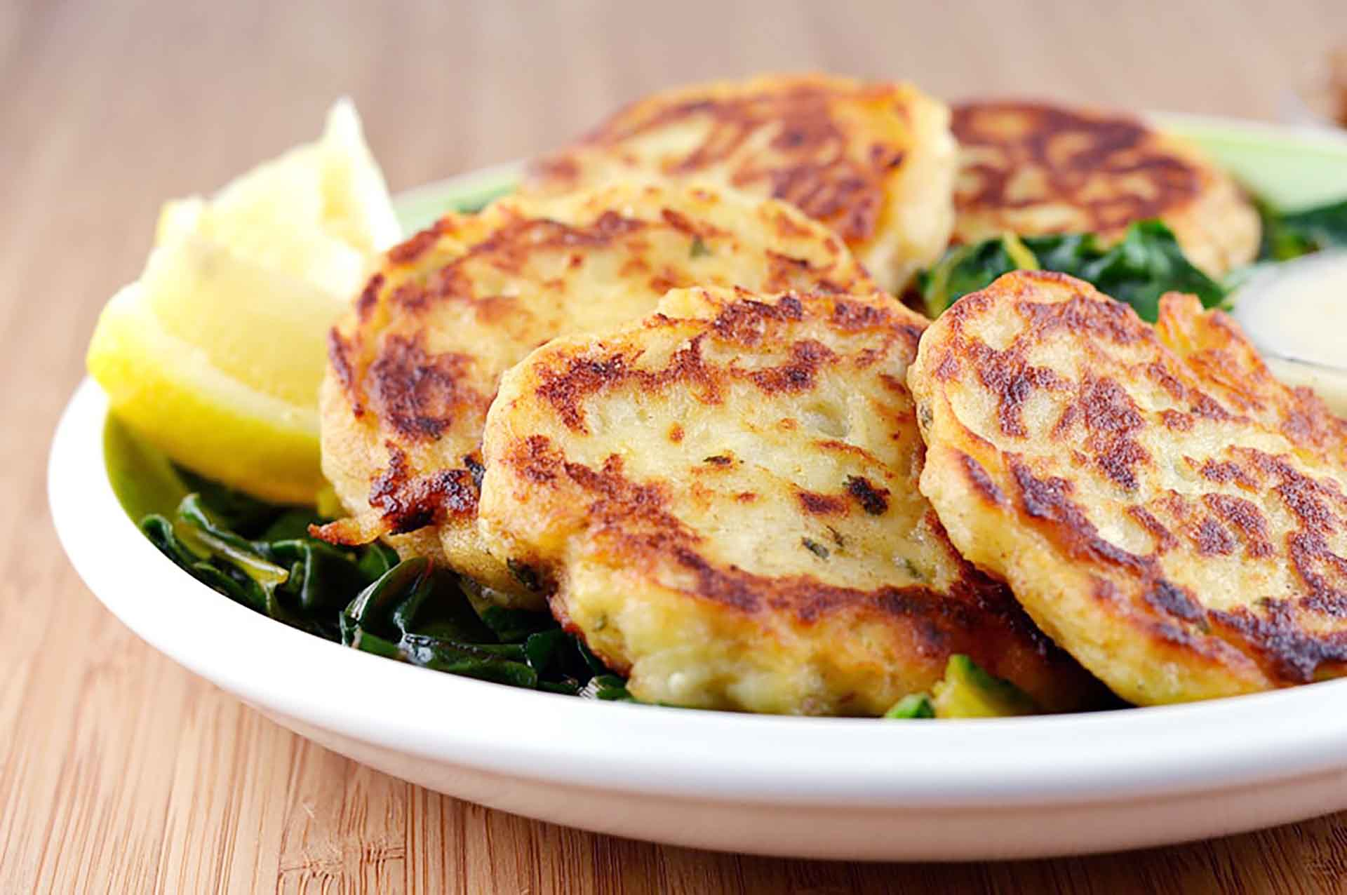 A plate of boxty sitting on a bed of greens