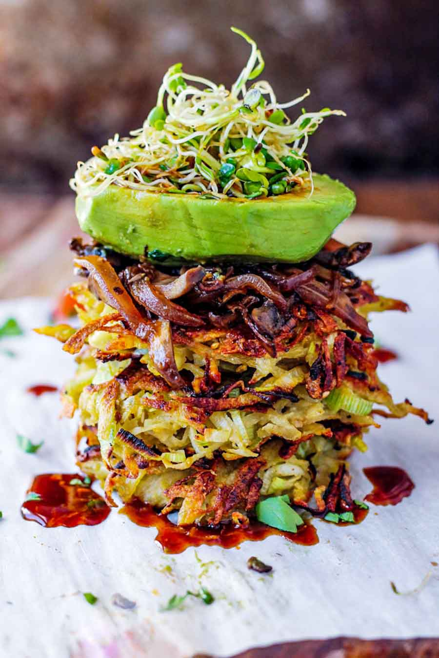 Potato & leek pancakes stacked on top of each other and topped with avocado and sprouts